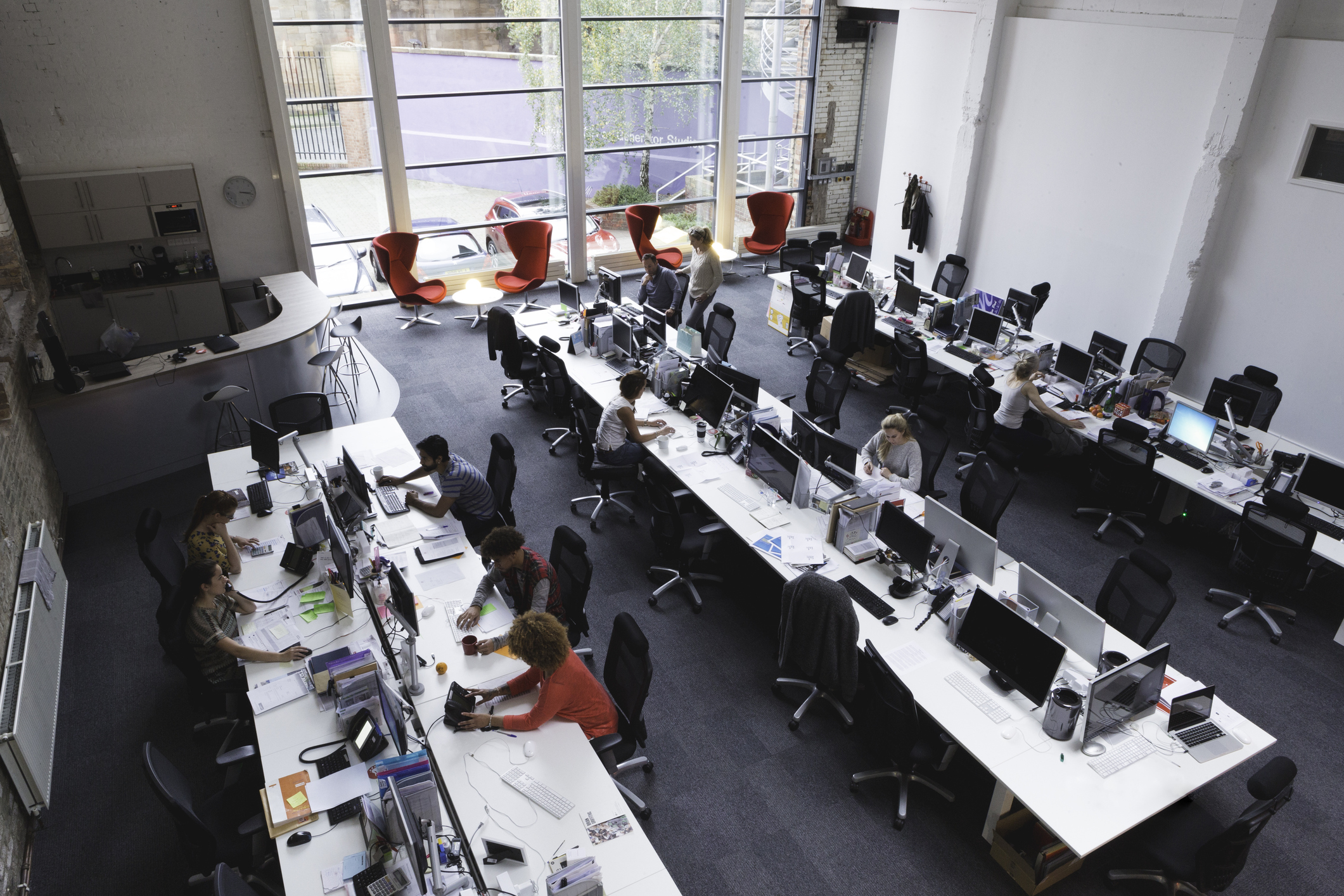 A horizontal image of a large office space shot from above. 10 office workers can be seen below. There are three large tables spread out across the room with multiple workstations.